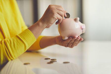 Photo pour Woman puts euro coin into piggy bank - image libre de droit