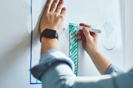 Photo pour Man draws graph with marker on white board at office - image libre de droit