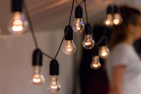 Photo pour Close up view of vintage decorative light lamp bulb glowing on the ceiling indoors. Transparent lamps glowing with warm light. - image libre de droit
