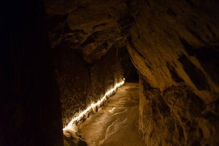 Photo pour Very old tunnel with illumination through mountain rock. - image libre de droit