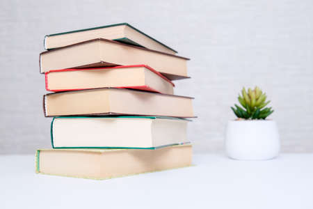 Photo for A stack of books lying on a white table, reading and education concept - Royalty Free Image