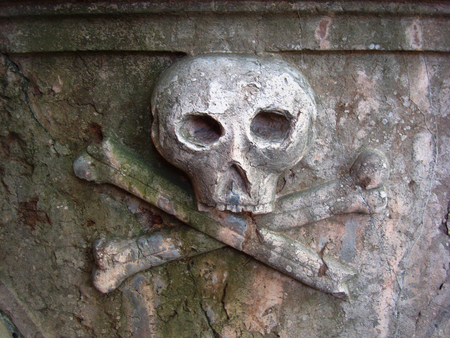 Skull and crossbones carving on a cemetery wall