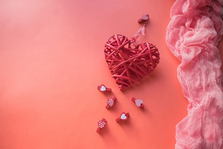Photo pour Valentines Day concept. Wicker heart and small clothespins with hearts on a coral background. field for text. - image libre de droit