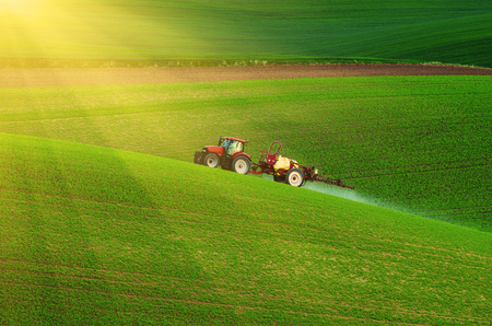 Photo for Farm machinery spraying insecticide to the green field, agricultural natural seasonal spring background - Royalty Free Image