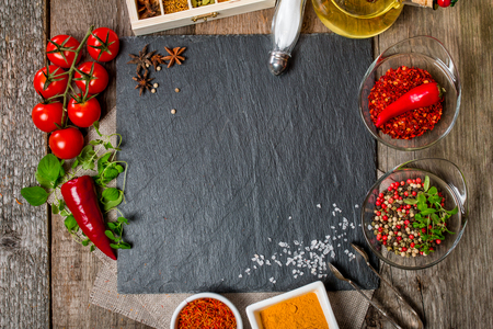 Food background, with space for text, herbs, spices, olive oil, salt, and vegetables. Slate and wood background. Top view