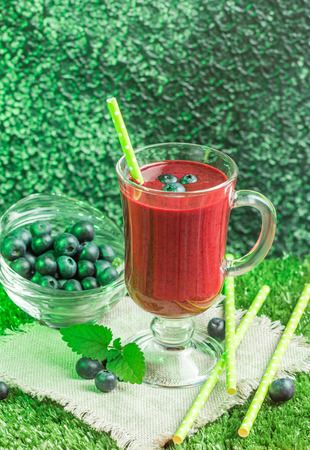 Blueberry smoothie in a glass on green background