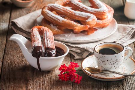 Foto de churros, coffee and hot chocolate on wooden table - Imagen libre de derechos