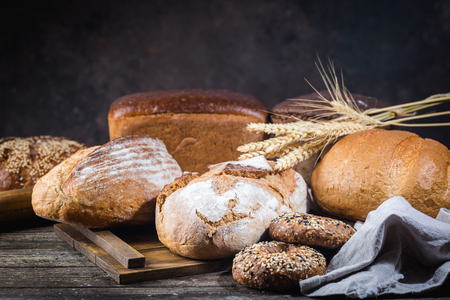 Photo pour Assortment of fresh baked bread and buns on wooden table background - image libre de droit