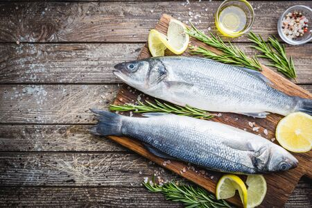 Photo pour Fresh raw seabass and ingredients for cooking. Two fish seabass with lemon, spices and herbs on wooden table, top view with copy space. - image libre de droit