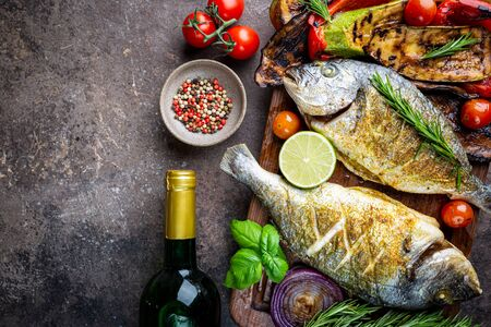 Photo for Baked Dorado fish, sea bream with grilled vegetables, herbs and seasonings, top view - Royalty Free Image