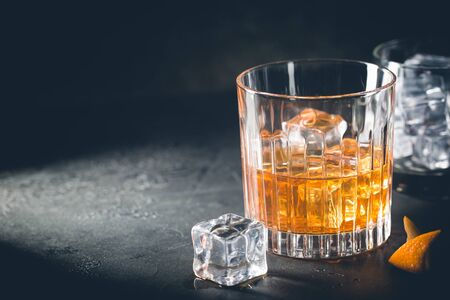 Photo pour Glass of scotch whiskey with ice cubes on black background - image libre de droit