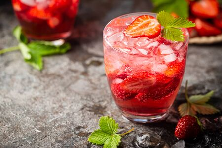 Photo pour Refreshing summer drink with strawberry slices in glasses on dark background - image libre de droit