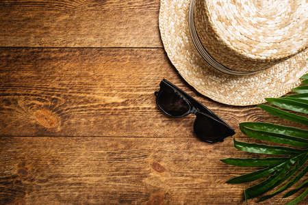 Foto per Straw beach hat and sun glasses top view on wooden background, summer flat lay - Immagine Royalty Free