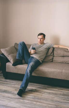 Photo pour Serious man having rest using smartphone sitting on sofa at home - image libre de droit