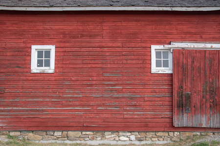 Photo pour Side of an old red barn with white framed square windows and sliding door. - image libre de droit
