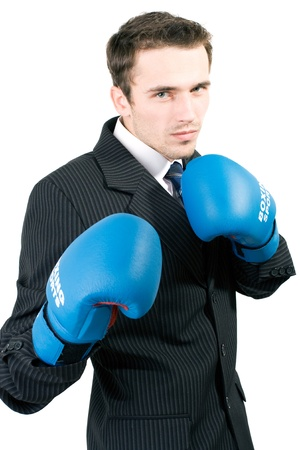 Handsome young man in suit and blue gloves boxing in office, made in studio isolated on white background