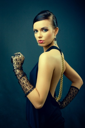 elegance dark hair woman fashion with gloves on hands, studio shot on dark blue background