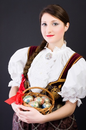 Beauty woman in traditional Polish clothes holding wicker basket with Easter eggs, Cieszyn Silesia region, studio shot