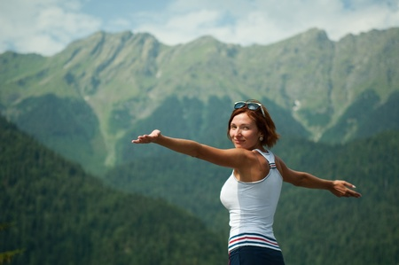 beautiful young girl in mountains rejoices  the space of freedom