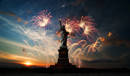 Statue of Liberty on the background of sunrise and fireworks