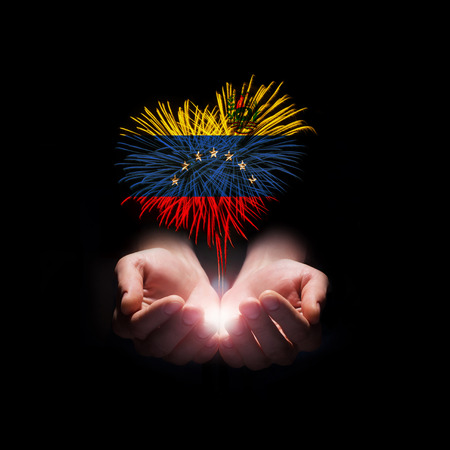 Fireworks in male hands in a heart shape with the flag of Venezuela