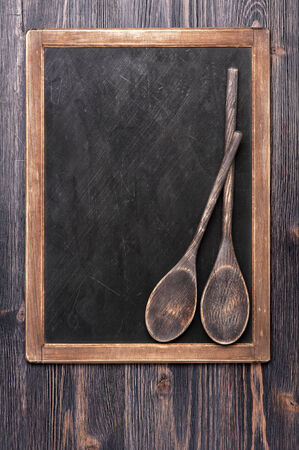 Black chalk board with old wooden spoons Serving