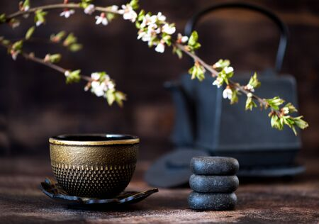 Photo for Black cast iron kettle, zen stones and a cup. Tea Asian concept - Royalty Free Image