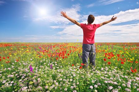 Man in spring meadow of flower. Emotional scene.