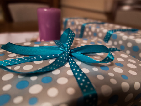 gifts wrapped in decorative paper and ribbon lying on the table