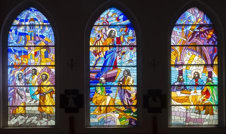Foto de Ozarowice, Poland, 22 April 2018: Colorful stained glass windows in the windows of the church in Ozarowicach in Silesia in Poland - Imagen libre de derechos