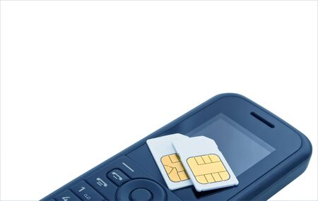 Two sim cards resting upon mobile telephone on white insulated background.