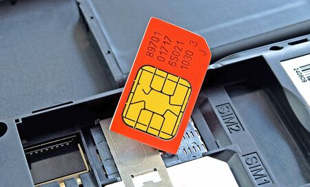 Sim card red colour, close-up, on background of the mobile telephone.