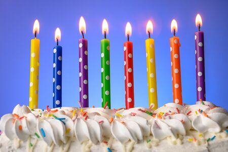 Photo pour multi-colored candles burn on a birthday cake on blue background - image libre de droit