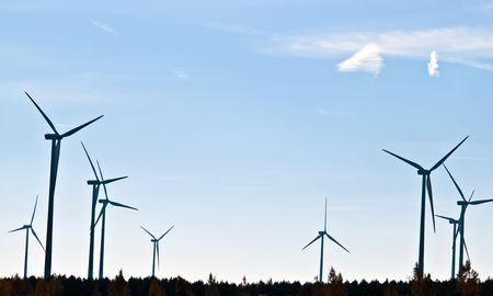 many wind turbines are on the field with blue sky