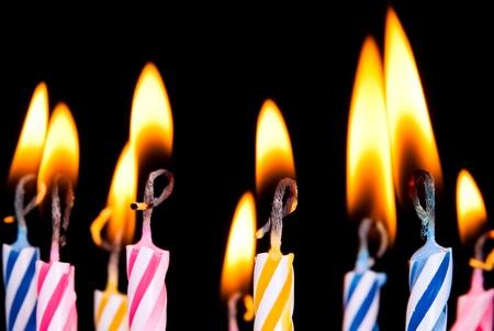 many coloured candles burn before black background