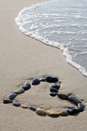 a heart of stones in the surge on the beach