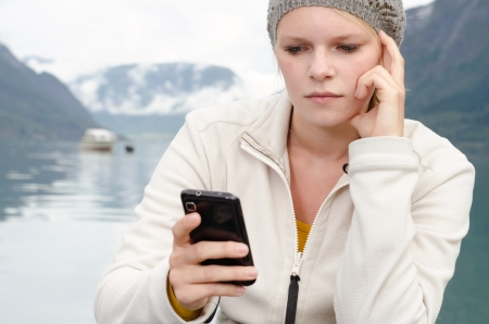 have young blond woman with her Smartphone in the hand and a fjord in Norway in the background