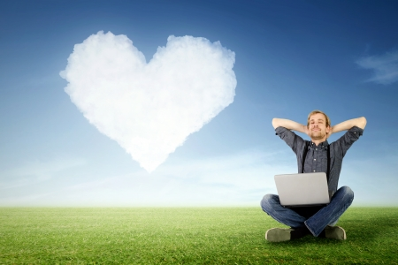 Photo pour a man sits relaxed with laptop on the meadow with a cloud in heart shape in the background - image libre de droit