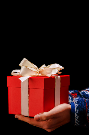 two hands hold a red present with white ribbon before black background
