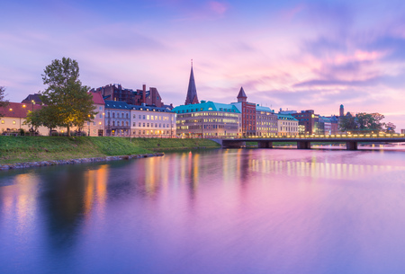 Beautiful sunset in Malmo, Sweden. Picturesque view of an old European city in the evening. Skyline reflected in the water. Long exposure photography