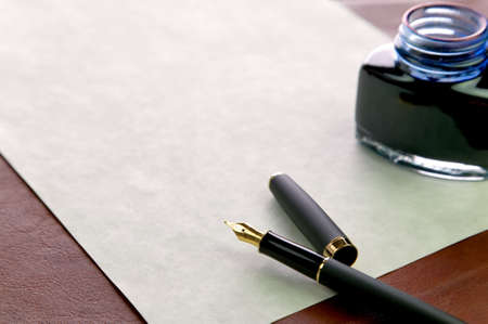 Gold nibbed fountain pen, watermarked expensive paper and an inkwell on a leather desk top, shallow DOF, focus on the nib.