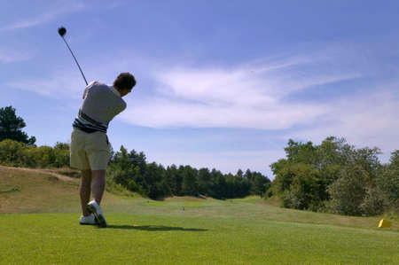 Shot of a male golfer teeing off with the ball in mid air on a bright sunny day, slight motion blur on the club.