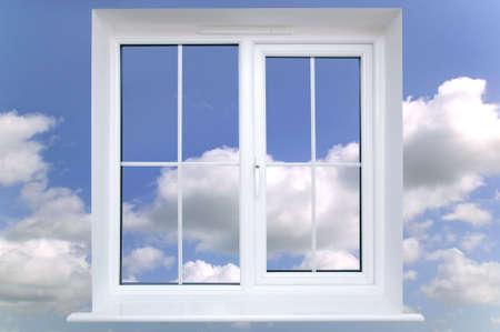 Window frame against a blue cloudy sky