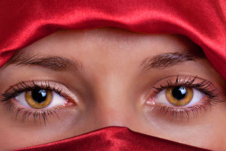 Close up of a pair of beautiful female brown eyes framed by a red silk veil.