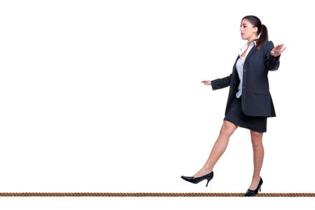 Businesswoman walking along a tightrope, isolated on a white background.