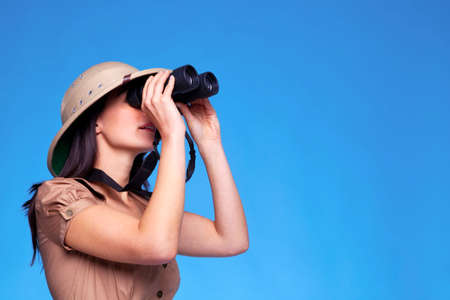 A woman wearing a pith helmet looking through a pair of binoculars, blue background with copy space.
