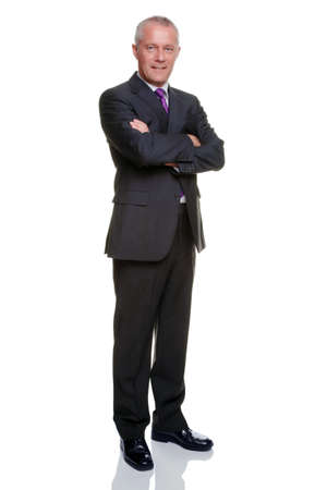 Full length shot of a mature businessman wearing a suit with his arms folded looking at camera.