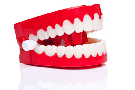 A pair of joke wind up chattering teeth on a pure white background, high resolution photo.