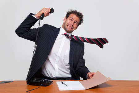 Businessman getting a phone call from an angry person shouting down the line.