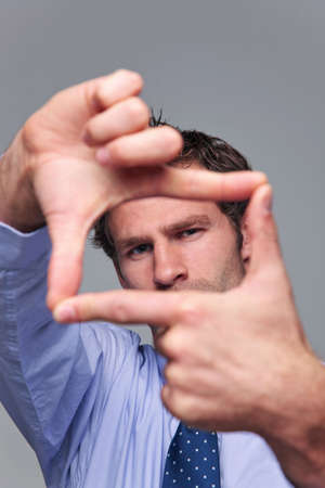 Businessman making a frame with his hands, focus on his face hands blurred.